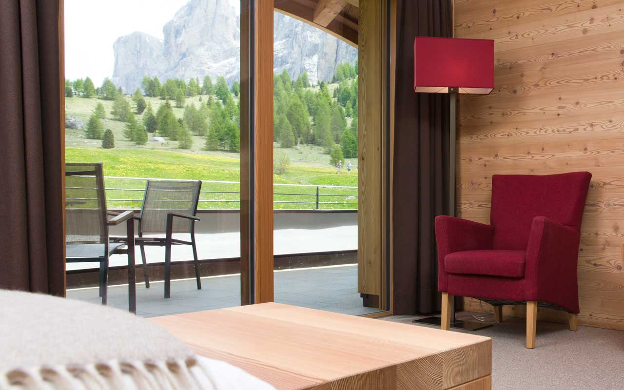 Red chair and red lamp with wood wall near French window with woods and Dolomites on the background