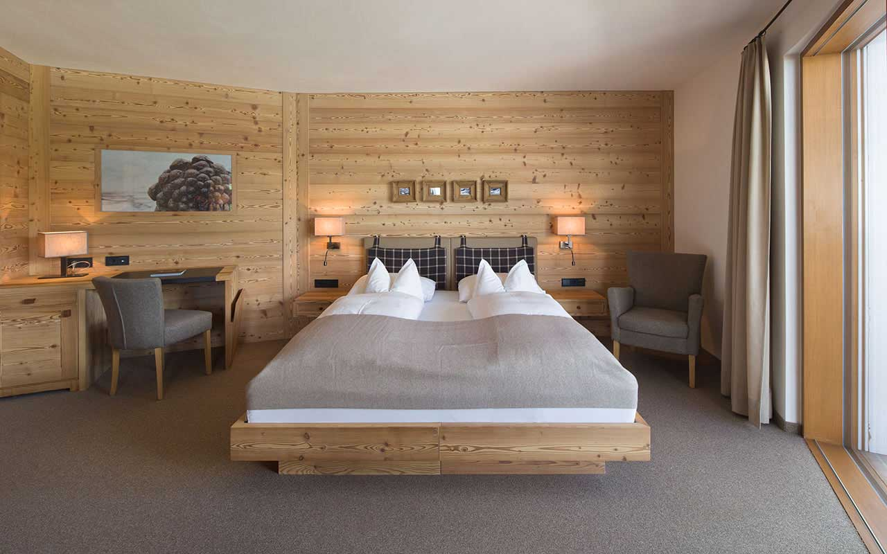 Bedroom with wood walls and double bed with white pillows and grey blankets
