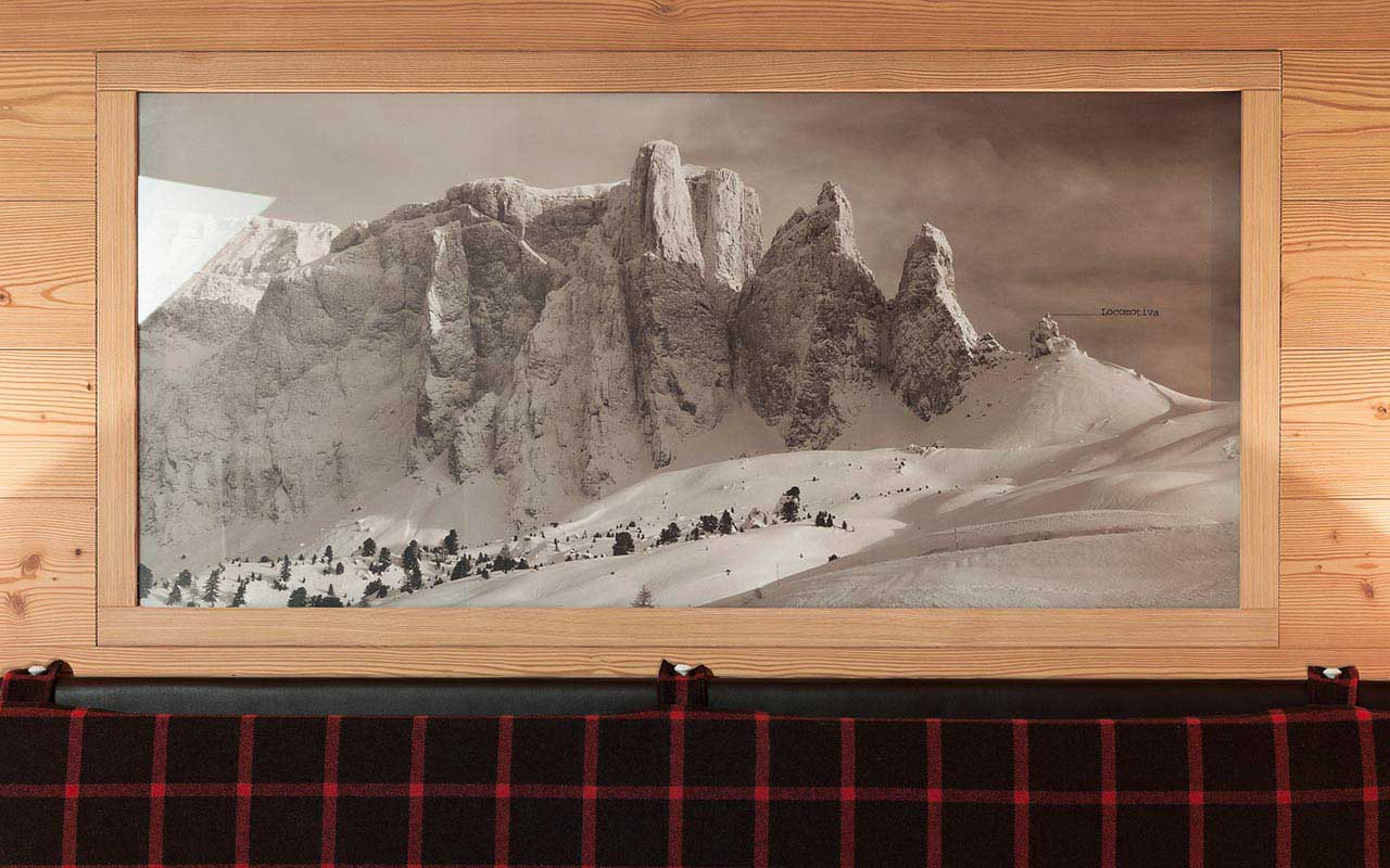 Picture hanging on the wall above headboard with snowy Dolomites in black and white