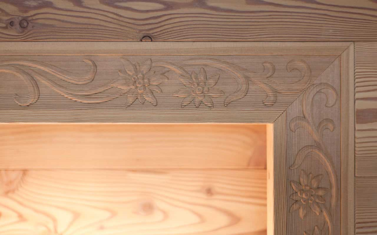Detail of wood corner decorated with edelweiss and illuminated from below