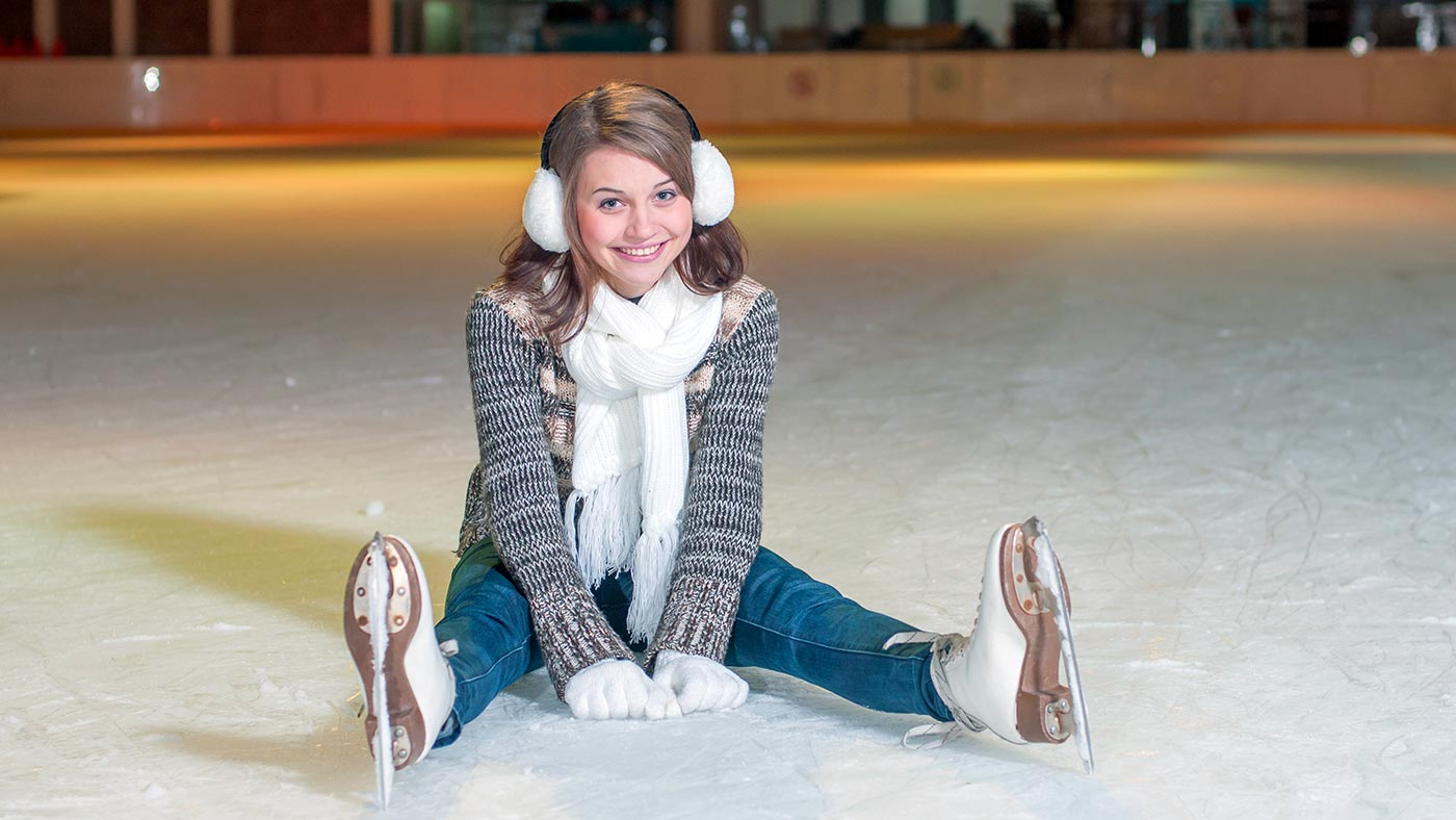 A girl sitting on a ice skating rink in Selva Val Gardena