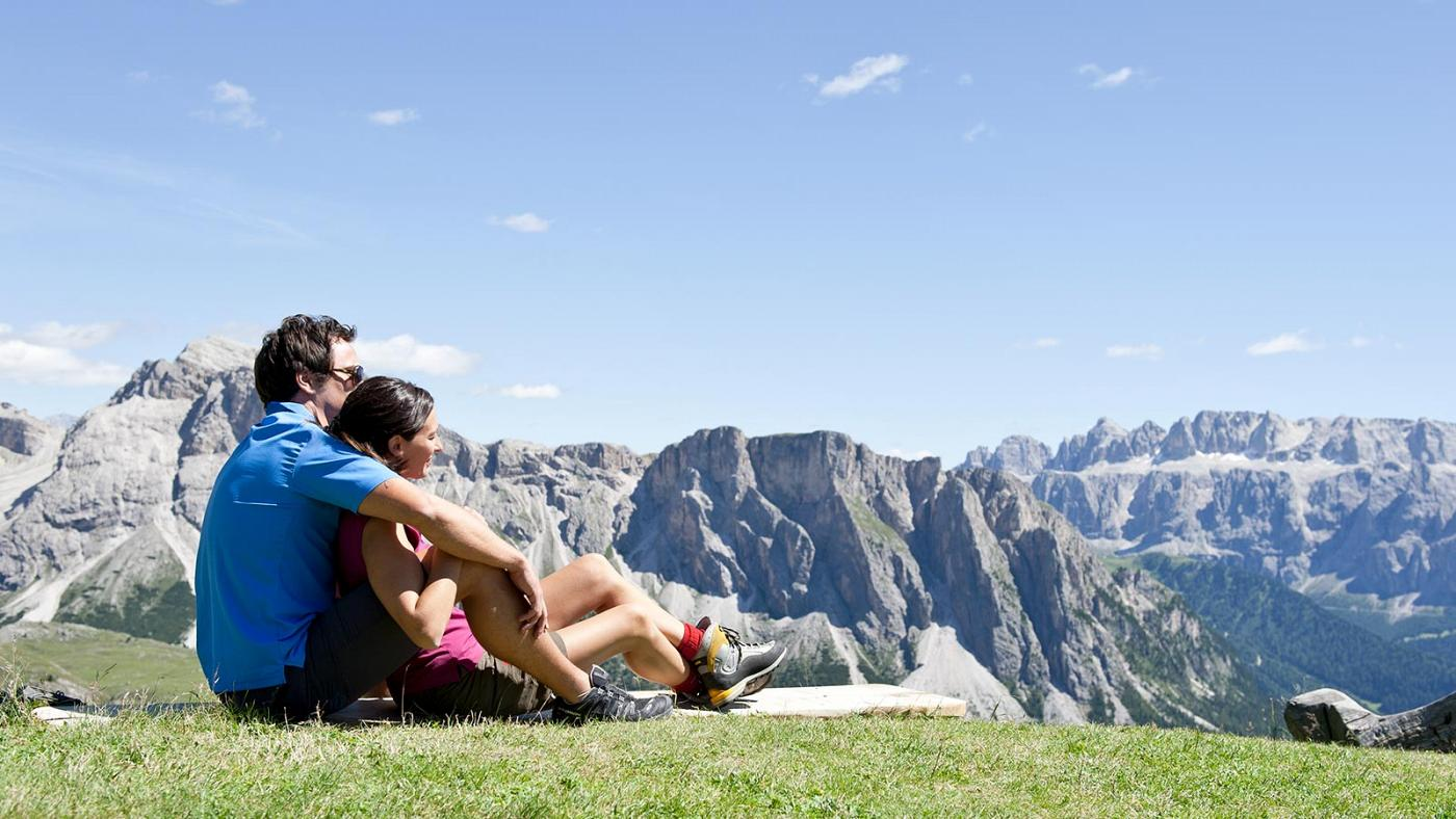 A couple enjoys the view across Sellaronda in Val Gardena Italy