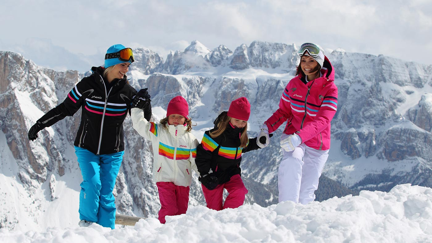 A family on the snow during a magic holiday in Val Gardena