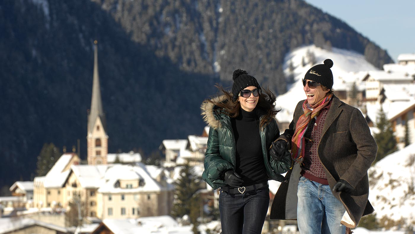 A couple walks on the snow in Selva Val Gardena